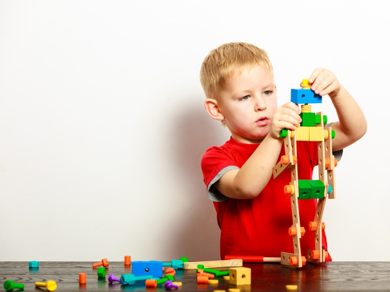12085459-little-boy-child-playing-with-building-blocks-toys-interior